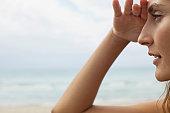 Woman at the beach, shading eyes and looking away
