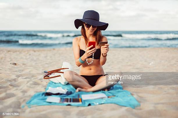 Woman at the beach shopping online with credit card
