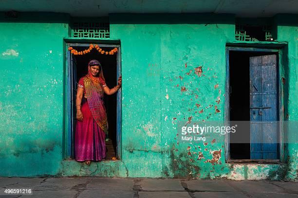 Woman at the doorstep of her colorful house in Mandu village Madhya Pradesh India