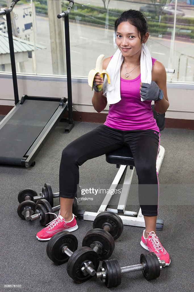 woman at the gym eating a banana : Stock Photo