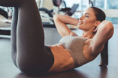 Attractive young woman is smiling while doing abs in gym