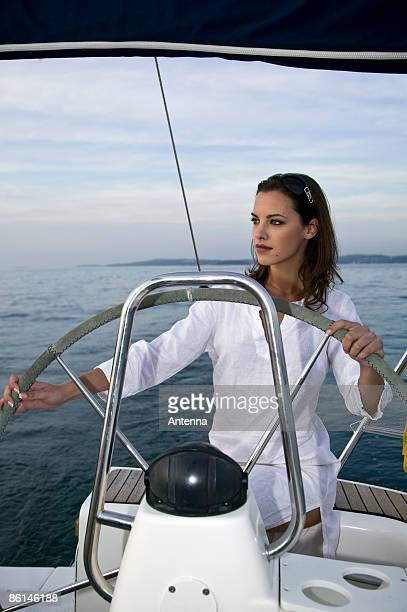 A woman at the helm of a yacht