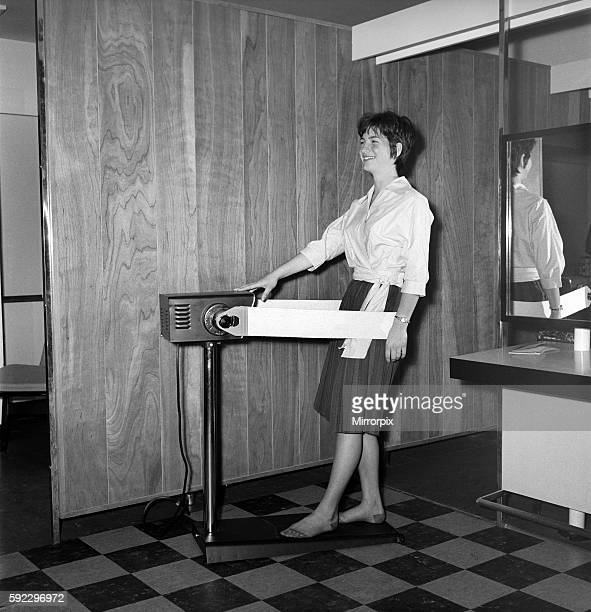 Woman at the John London Hair and Beauty Saloon seen here using a band vibrating slimming machine that tones the thigh muscles 1960