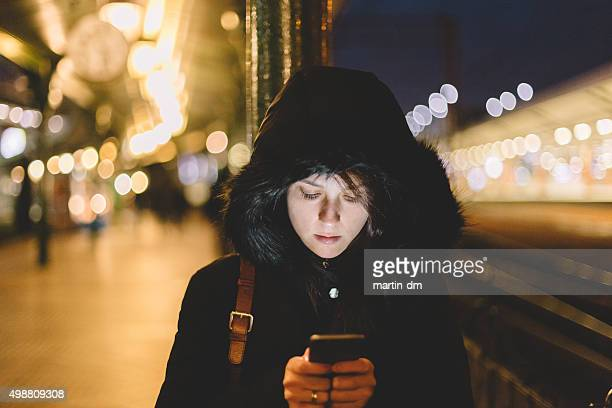 Woman at the railway station texting on smartphone
