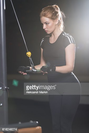 Woman at the sport gym doing arms exercises on a : Stock Photo