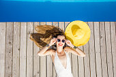 Playful woman lying with yellow sunhat on the poolside. Summer vacation concept