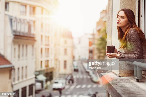 Woman at the window with a cup of coffee
