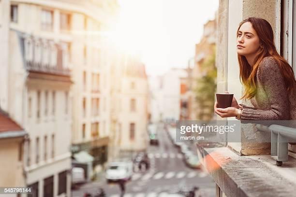 Donna alla finestra con una tazza di caffè