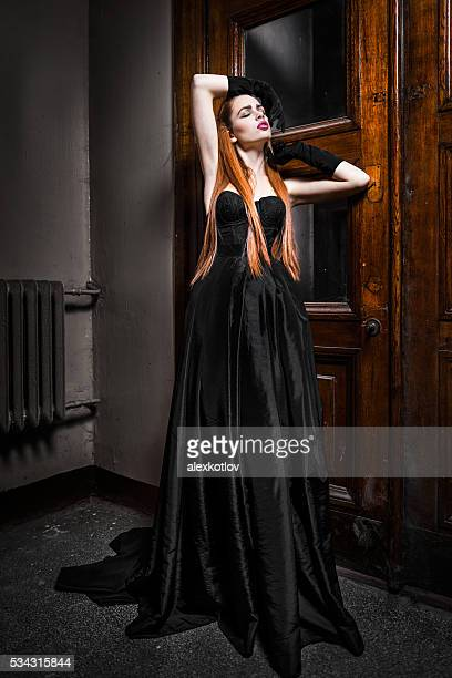 Woman at the wooden door in gothic styled dress