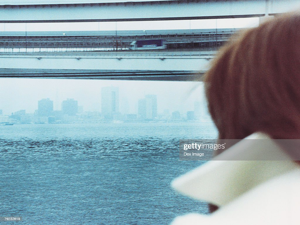 Woman at waterfront, rear view : Stock Photo