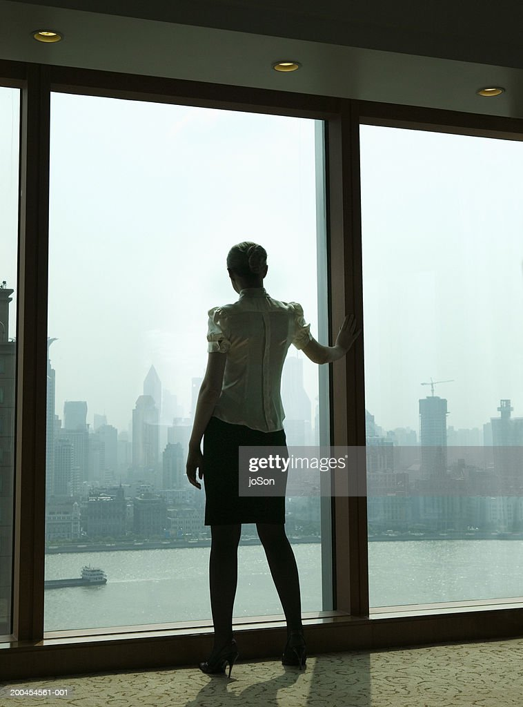 Woman at window, rear view, sunrise : Stock Photo