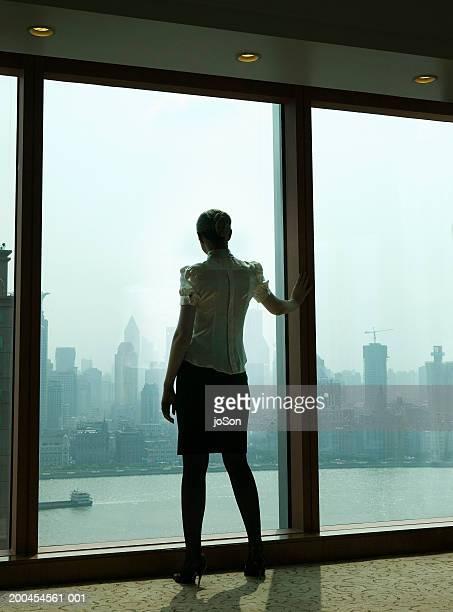 Woman at window, rear view, sunrise