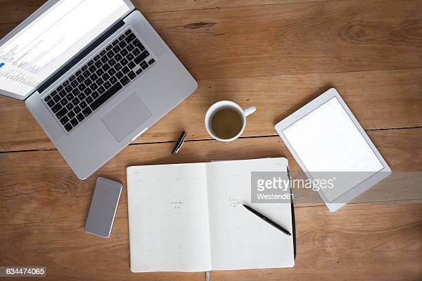 Woman at wooden table using smartphone and writing in notebook
