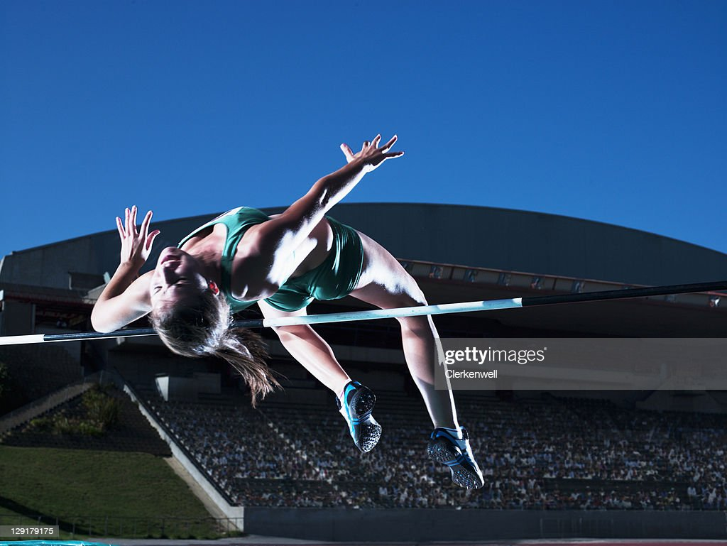 Woman athlete clearing high jump : Stock Photo