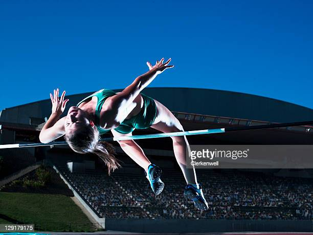 Woman athlete clearing high jump