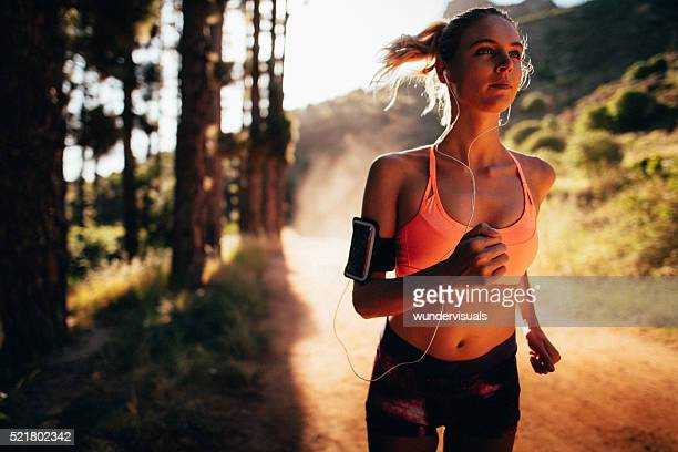 Woman athlete running on a nature trail in early morning