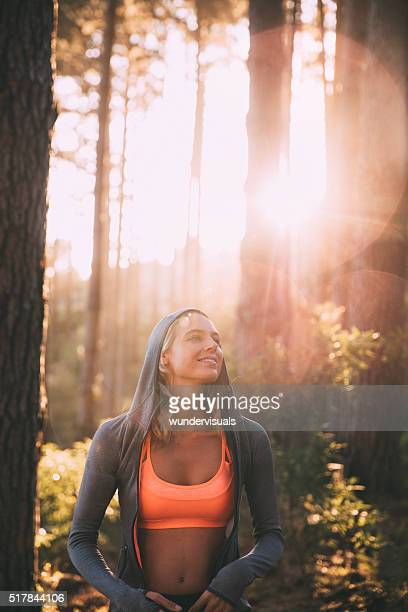 Woman athlete smiling in a forest with morning sunflare