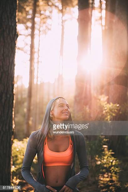 Frau Athlet lächelnd in einem Wald mit Morgen SunFlare