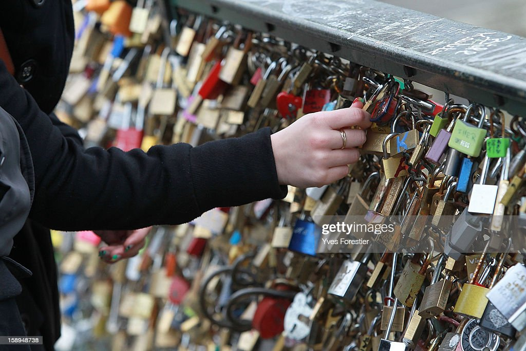 A woman attaches a padlocks to the Pont des Arts on January 4, 2013 in Paris, France. The nine-arch metallic footbridge completed in 1804 is one of the most romantic places of the capital where people visit it to attach love padlocks illustrated with their initials or messages of love, before throwing the key into the River Seine. The bridge is also a meeting place for artists who find inspiration from the surrounding views of the city.