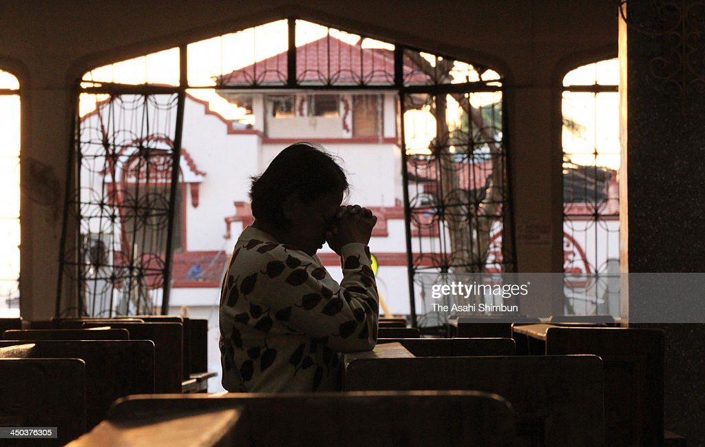 A woman attends a Sunday mass at a Typhoon Haiyan demolished church on November 17, 2013 in Tacloban, Leyte, Philippines. Typhoon Haiyan which ripped through Philippines over the weekend has been described as on of the most powerful typhoons ever to hit land, leaving thousands dead and hundreds of thousands homeless. Countries all over the world have pledged relief aid to help support those affected by the typhoon however damage to the airport and roads have made moving the aid into the most affected areas very difficult. With dead bodies left out in the open air and very limited food, water and shelter, health concerns are growing.