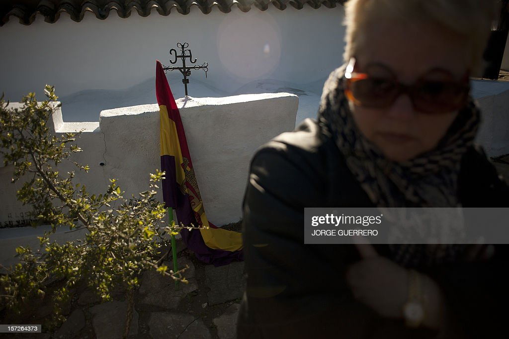 A woman attends the funeral ceremony for 28 people executed during the Spanish Civil War at La Sauceda Cemetery in Cortes de la Frontera on December 1, 2012. Twenty-eight, seven women and 21 men, of the hundreds of people who were tortured and executed by the forces of Francisco Franco at the 'El Marrufo Estate' in Cadiz during the Spanish Civil war, received a proper burial today, 76 years after their bodies, all shot, were thrown into mass graves.