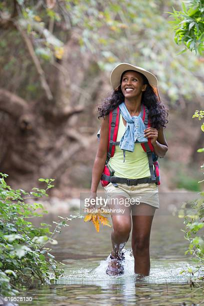 Woman backpacker wading creek in forest.