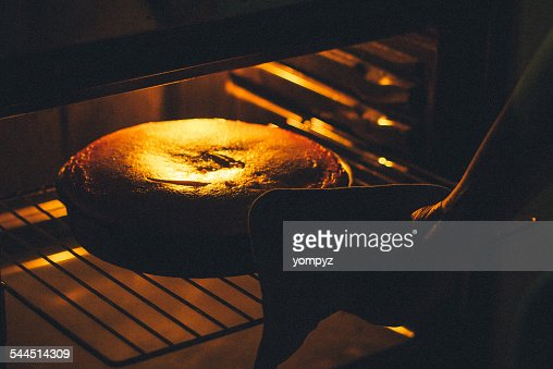 Woman baking cake in oven