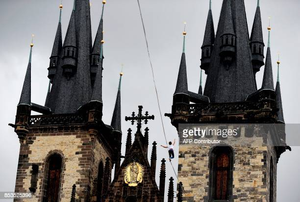 A woman balances on a rope attached highly over the Old Town square as part of the 'Zivot na hrane' campaign supporting people diagnosed with...