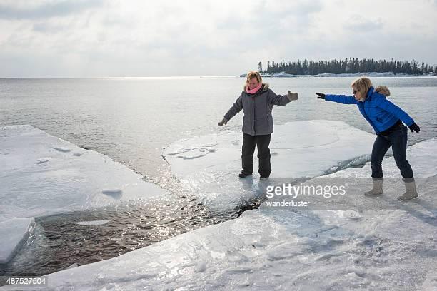 Woman balances on ice floe floating in Lake Superior