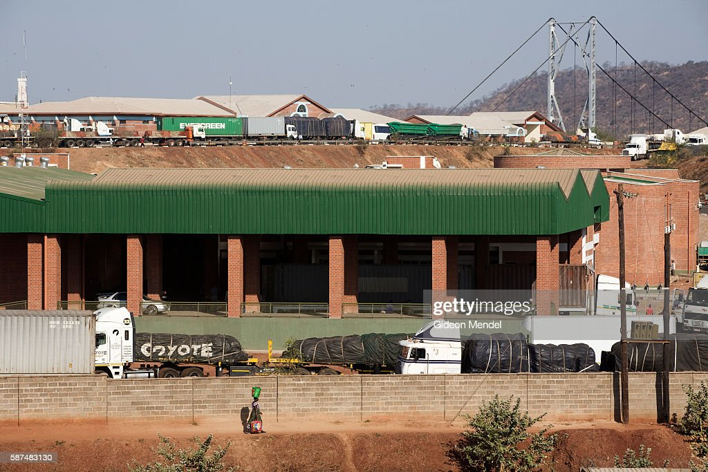 A woman balancing a load of water on her head walks past the new customs building in Chirundu on the border of Zambia and Zimbabwe In the background...