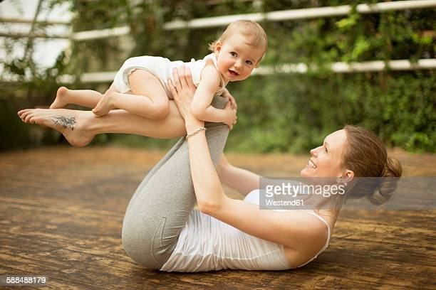 Woman balancing baby on her legs