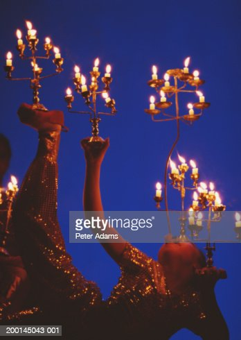 Woman balancing candles on hand's, feet and face