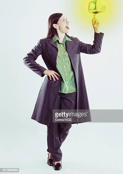 Woman Balancing Mini Computer Monitor on Fingertip