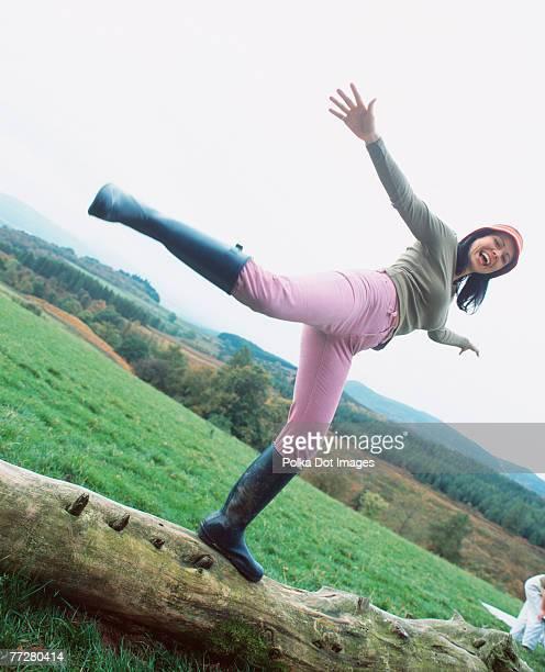 Woman balancing on a log in rural setting