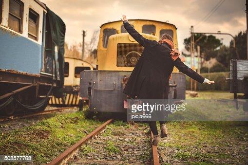 Woman balancing on a railroad track : Stockfoto