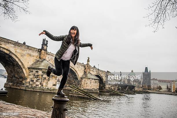 Woman balancing on bollard in front of Charles Bridge, Prague