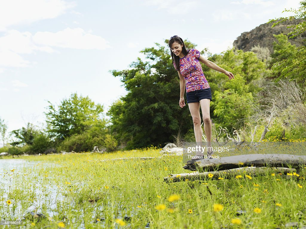 Woman balancing on log by river : Stock Photo