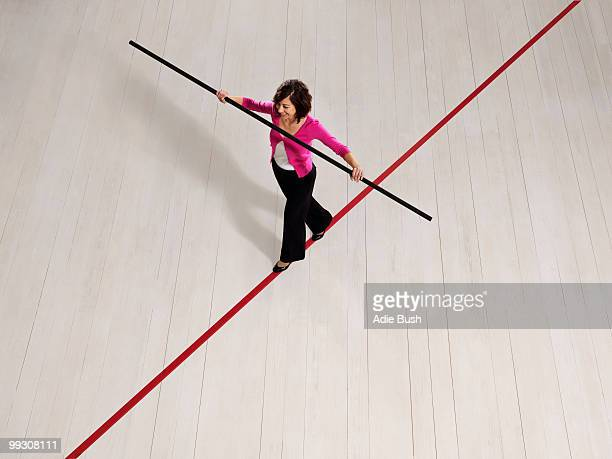 Woman balancing on thin red line