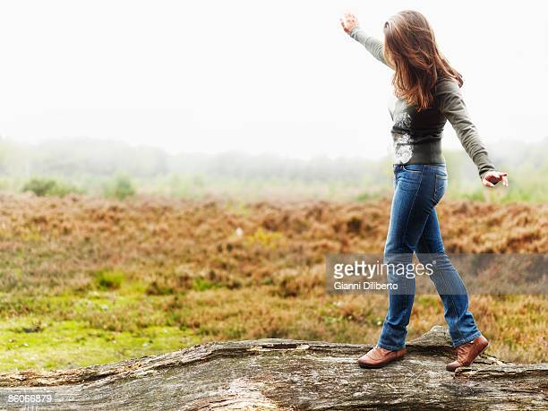 Woman balancing on tree branch in field