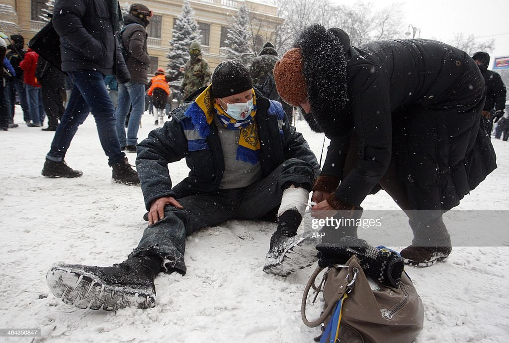 A woman bandages a wounded demonstrator's leg during clashes between protestors and police in the centre of Kiev on January 22, 2014. Ukrainian police today stormed protesters' barricades in Kiev as violent clashes erupted and activists said that one person had been shot dead by the security forces. Total of two activists shot dead during clashing. The move by police increased tensions to a new peak after two months of protests over President Viktor Yanukovych's failure to sign a deal for closer ties with the EU.