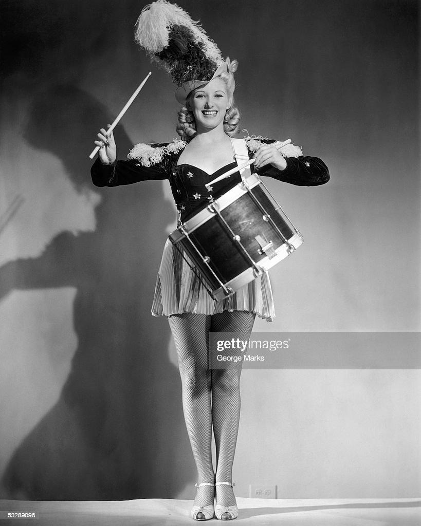 Woman banging on drum : Stock Photo