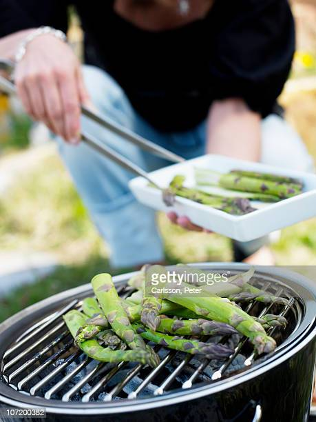 Woman barbecuing asparagus, close-up