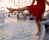 Woman barefoot on fountain, in piazza