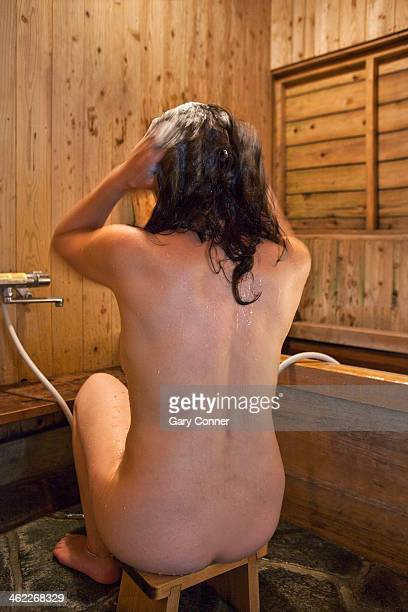 Woman bathes before soaking in hot bath