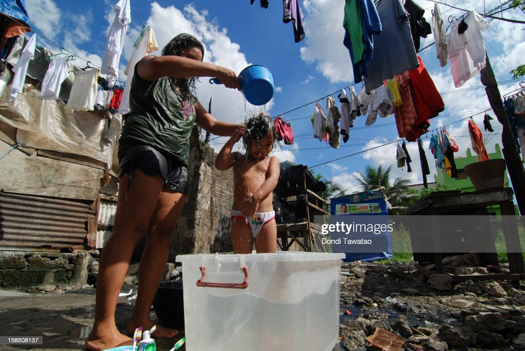 A woman bathes her daughter at a slum district on December 18, 2012 in Manila, Philippines. The Philippines Congress recently passed the Reproductive Health Bill allowing women with more choice in family planning and access to education on sexual health. The Bill has been passed amidst strong opposition from the Church and has been seen as a landmark decision in what is considered a deeply conservative Catholic country. Reproductive health care supporters say the vital measure will help the poor which account for almost half the population of around 91 million people.