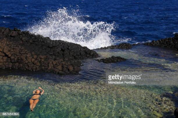 A woman bathing belly up in the lake of the Ondine a smallest green lake filled up by the sea wakes located on the rocks near the lighthouse of Punta...