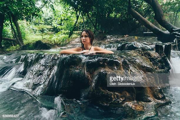 Woman bathing in hot spring waterfall