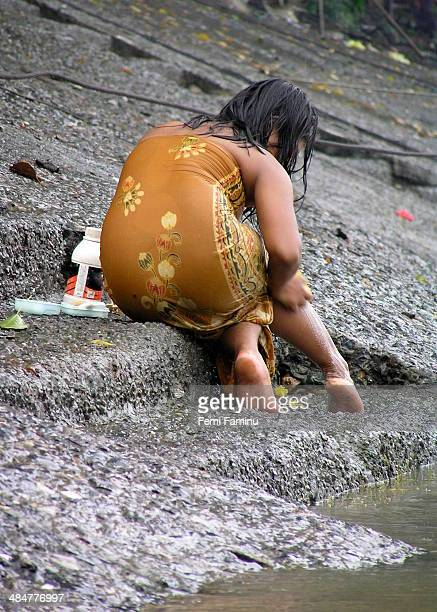 Woman bathing on banks of Irrawaddy river