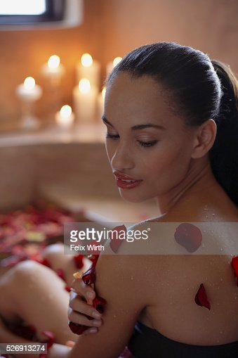 Woman bathing with flower petals : Stockfoto