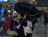 A woman battles the high winds with her umbrella as she walks across a bridge in central London on February 12 2014 Flooded communities in Britain...
